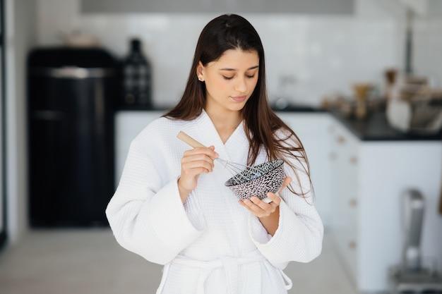 Elegante donna sorridente in camice bianco che prepara cibo