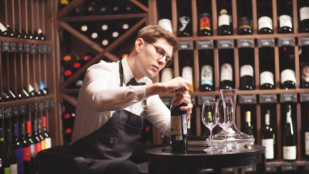Elegant sommelier with a bow tie uncorks a bottle of wine in a wine boutique