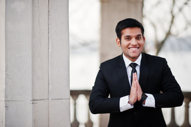 Elegant south asian business man in suit show namaste hands.