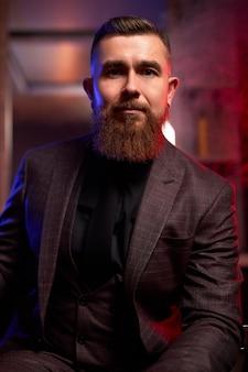 Elegant stylish business man in formal costume sits in dark room