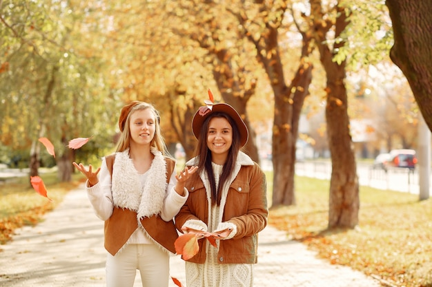 Elegant and stylish girls in a autumn park