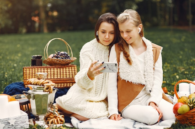 Elegant and stylish girls sitting in a autumn park