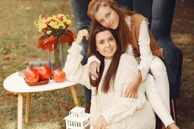 Elegant and stylish girls sitting on a chair in a park