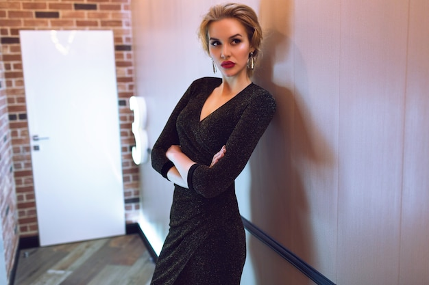 Элегантная стильная дама в длинном вечернем сверкающем платье позирует в коридоре отеля, эффект фильма, тонированные мягкие цвета, роскошная жизнь.