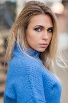 매력적인 미소로 우아하고 세련된 여성이 카메라에 보인다. 봄에 거리에 포즈를 취하는 파란색 옷을 입은 소녀