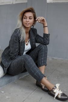 거리에서 회색 벽 근처에 앉아 빈티지 회색 양복에 우아한 세련 된 젊은 여자. 패션