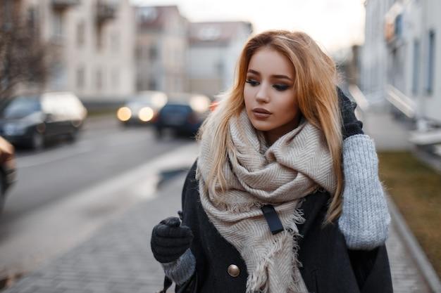 현대적인 건물을 배경으로 거리를 걷고 유행 가을 옷에 우아한 세련 된 젊은 여자. 유행 아름다운 소녀.
