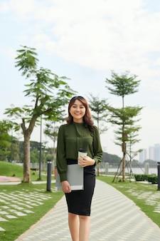コーヒーを飲みながら屋外を歩くエレガントな成功した bsuiness の女性