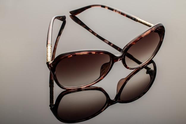 Elegant sunglasses on grey
