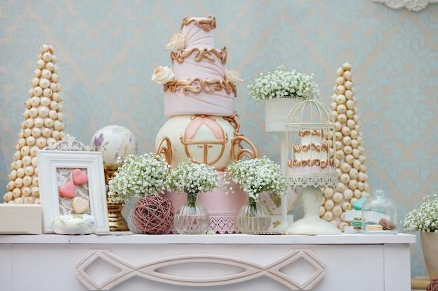 ディナーまたはイベントパーティーでの大きなケーキとマカロンのエレガントな甘いテーブル