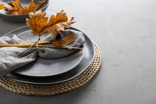 Элегантная сервировка стола с осенними дубовыми листьями и золотыми столовыми приборами.