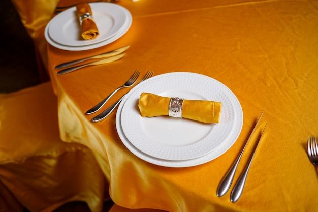 Элегантная сервировка стола вилкой, ножом и золотой салфеткой