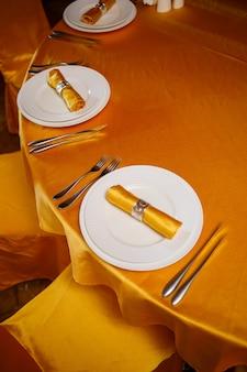 フォーク、ナイフ、ゴールドナプキンを備えたエレガントなテーブルセッティング