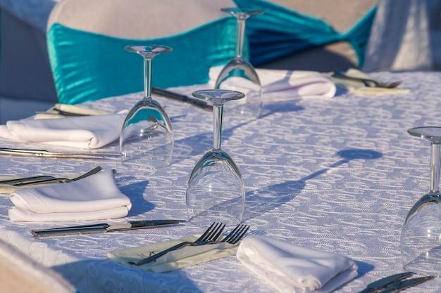 레스토랑에서 포크, 나이프, 와인 잔, 냅킨이 있는 우아한 테이블 설정. 저녁 식사를 위해 배열된 은제품과 냅킨이 있는 멋진 식탁 세트, 터키, 클로즈업
