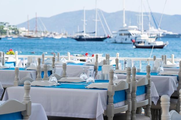 레스토랑에는 포크, 나이프, 와인 잔, 흰색 접시, 파란색 냅킨이 있는 우아한 테이블 설정이 있습니다. 터키 보드룸(bodrum) 저녁 식사를 위해 은그릇과 냅킨을 배치한 멋진 식탁. 바다 근처 해변 카페