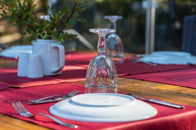 레스토랑에서 포크, 나이프, 와인 잔, 흰색 접시, 빨간색 냅킨이 있는 우아한 테이블 설정. 저녁 식사를 위해 배열된 은제품과 냅킨이 있는 멋진 식탁 세트, 터키