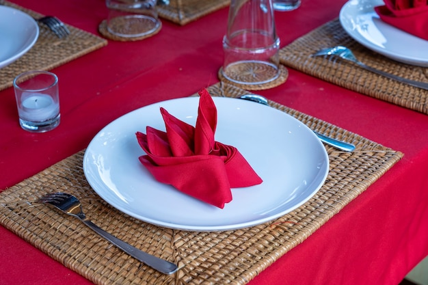 レストランのフォーク、スプーン、白いプレート、赤いナプキンのエレガントなテーブルセッティング、クローズアップ。銀器とナプキンを並べた素敵なダイニングテーブル