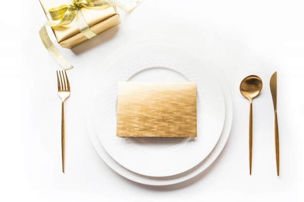 Elegant table setting with golden cutlery on white. top view.