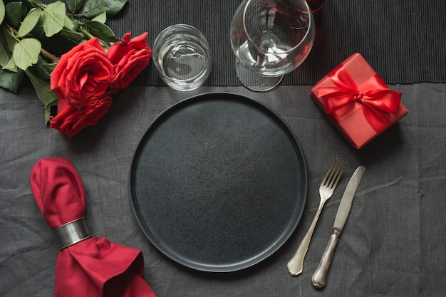 Elegant table setting with red rose on black linen tablecloth.
