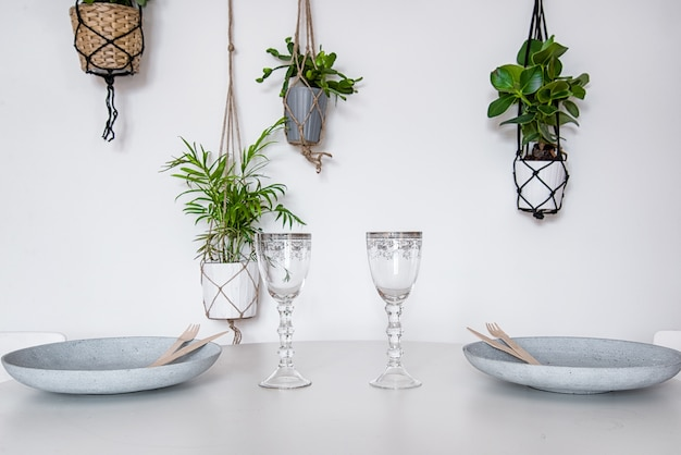 Elegant table setting with wine glasses, plates and house plants hanging on the wall