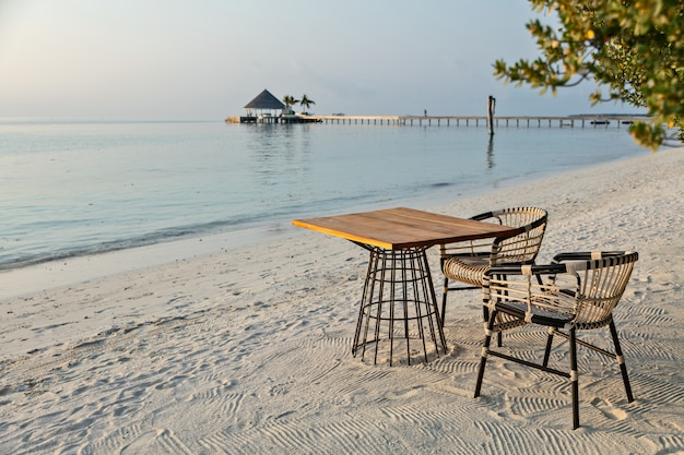 Elegant table and two chairs on sandy beach, romantic vacations