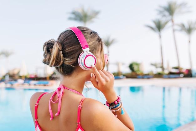 Elegante ragazza abbronzata con acconciatura carina in piedi davanti alla grande piscina all'aperto pronta a nuotare nella mattina di sole
