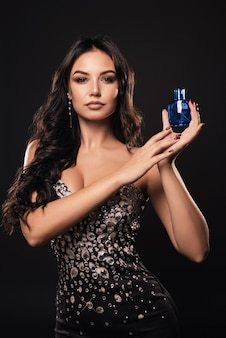Элегантная загорелая женщина в красивом платье с духами