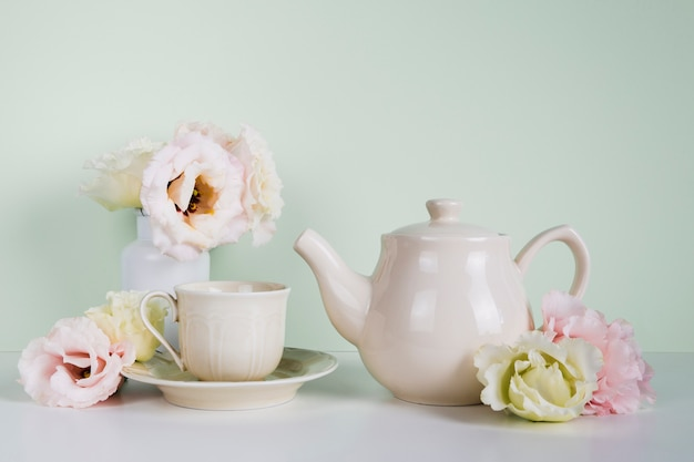 Elegant tea pot next to flowers