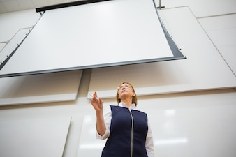 Elegant teacher with projection screen in the lecture hall