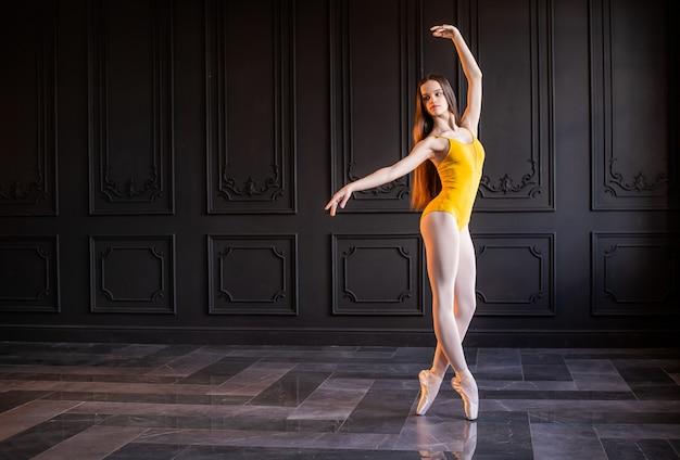 짙은 회색 실내에서 춤추는 노란색 레오타드의 포인트 슈즈에 우아한 십대 발레리나