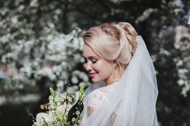 屋外の花の花束を持つエレガントな優しい花嫁。結婚式の日