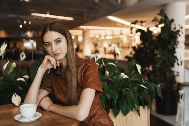 Элегантная задумчивая молодая соблазнительная женщина сидит в одиночестве в кафе, опираясь на ладонь, глядя в камеру с серьезным взглядом.