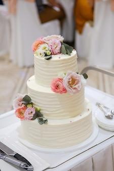 白い木製のテーブルに、自然の花やバラと緑の葉で飾られたエレガントな3段の白いウェディングケーキ。近くには、切断用のカトラリー、プレートがあります。