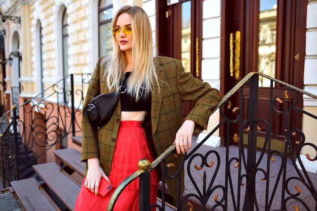 Elegante donna bionda alla moda in posa sulla strada vicino al bellissimo edificio antico, indossando occhiali da sole e abbigliamento alla moda alla moda hipster, stile primavera autunno.