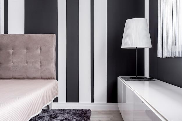 Элегантная тафтинговая кровать и лампа с абажуром в черно-белой комнате