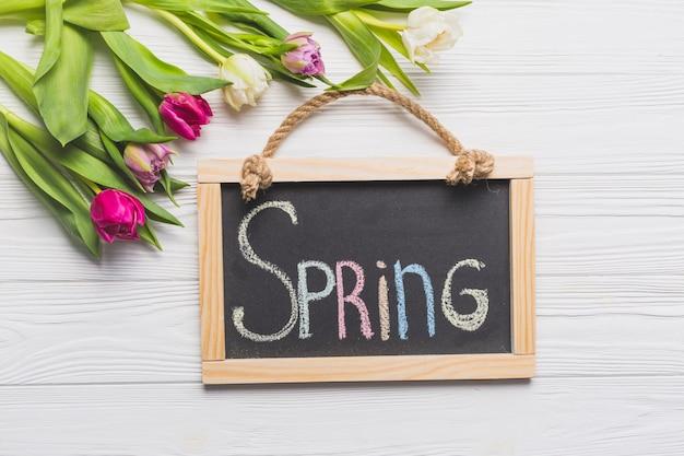 Tulipani eleganti vicino alla scrittura di primavera