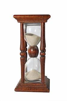 Элегантные старинные песочные часы с просачивающимся белым песком, изолированным на белой поверхности.