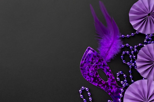 Elegant violet mask and decorations on dark background