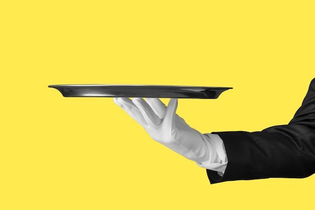 Элегантная рука официанта в белой перчатке, держащая пустую тарелку с пустым градиентным фоном.