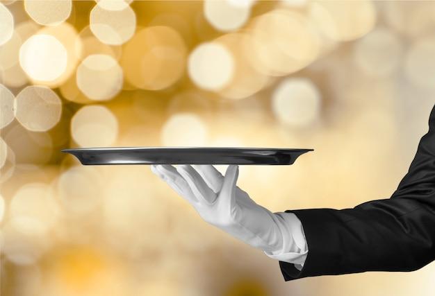 Элегантная рука официанта в белой перчатке держит пустую тарелку