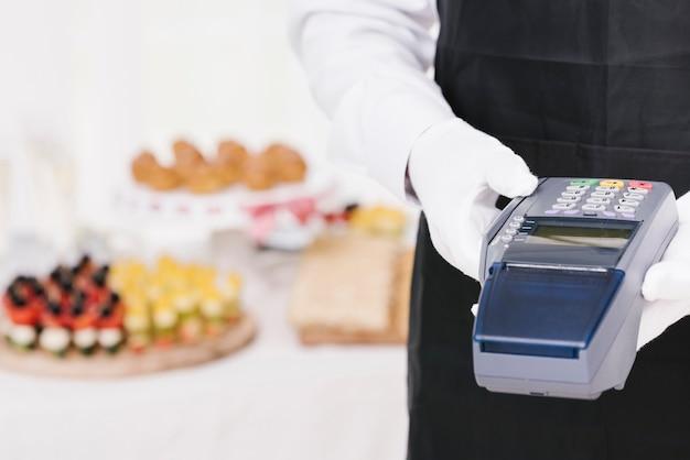 Cameriere elegante che tiene un dataphone