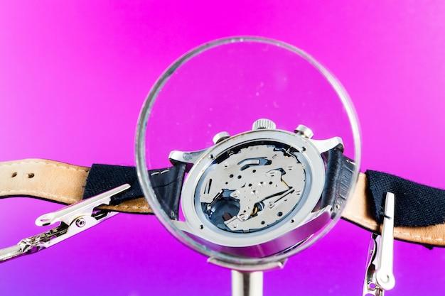 Элегантные часы отремонтированы с помощью лупы с тремя ручками