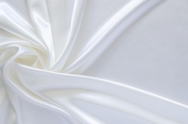 우아한 물결 모양과 부드러운 흰색 새틴 천 질감 배경