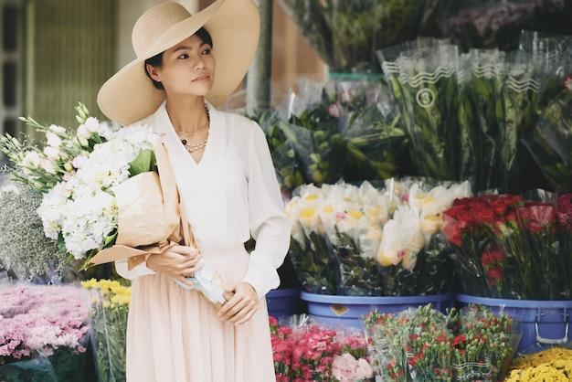 큰 꽃다발을 가진 우아한 부유 한 아시아 아가씨가 꽃 가게 밖에서 기다리고 있습니다.