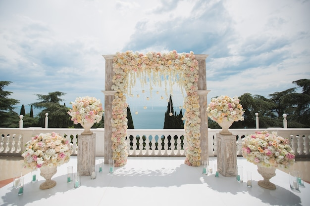 Элегантная свадебная арка с живыми цветами, вазами на фоне океана и голубого неба.