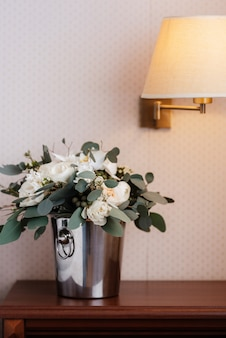 Elegant wedding bouquet of fresh flowers and greenery in a bucket