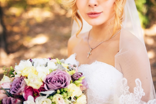 Elegant wedding bouquet in the hands of the bride. bouquet with lilac, white, pink roses. wedding bouquet in the autumn forest