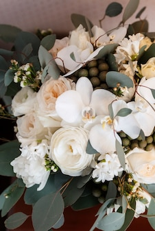 バケツの中の新鮮な花と緑のエレガントなウェディングブーケ