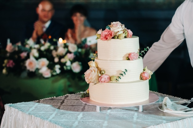 Elegant wedding cake at the wedding in three tiers.