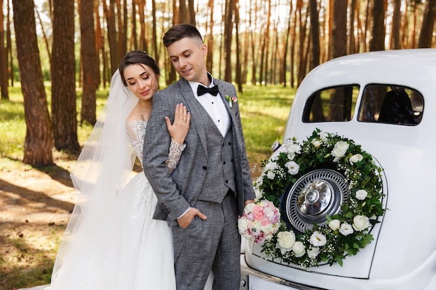 Elegant wedding couple, bride and groom embracing near white just married car with decoration of wreath with fresh flowers
